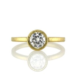 the gold solitaire bezel-set . ring