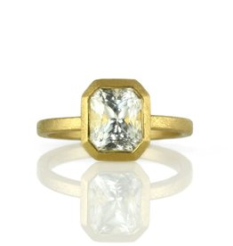 the gold solitaire bezel-set (emerald-cut) . ring