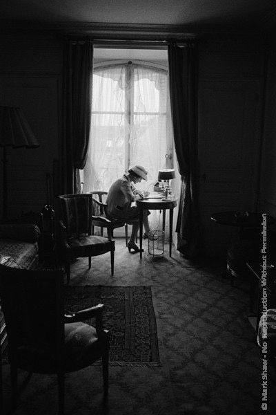 Mark Shaw Photography - Coco Chanel Writes at Desk in Window, Head Down 1957