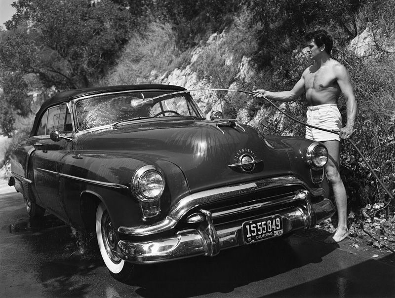 Rock Hudson washing his 1952 Oldsmobile outside of his North Hollywood home 1952 - Sid Avery