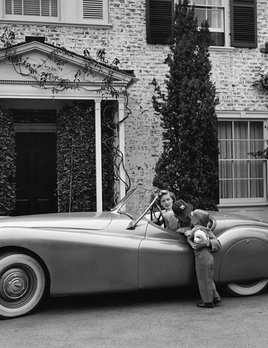 Humphrey Bogart, Lauren Bacall and their son, Stephen, in their Jaguar XK 120 at home in Los Angeles, CA 1952 - Sid Avery