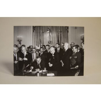 Historic black and white postcard of President Johnson signing the Civil Rights Act of 1964, joined by Dr. Martin Luther King, Jr. This landmark piece of legislation outlawed major forms of discrimination against racial, ethnic, national and religious min