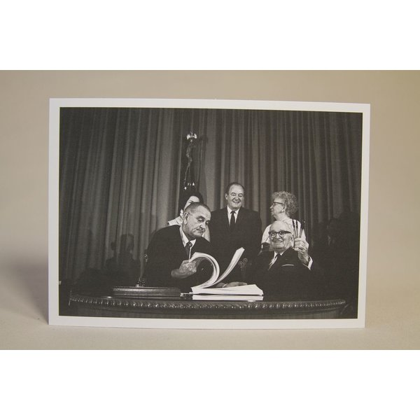 All the way with LBJ Black and white postcard of President Johnson signing the Medicare Bill with former President Truman, Lady Bird Johnson, Vice President Hubert Humphrey, and Bess Truman.