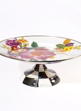 Mackenzie-Childs Our Flower Market Enamel Small Pedestal Platter is certain to be the center of attention at every gathering. The color-glazed serving dish is decorated with hand-applied fanciful botanical transfers that recall a lush English garden in the peak of summer,