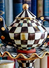 Mackenzie-Childs Who doesn't love the cozy charm of an old-fashioned teapot. This chubby charmer crafted of clay and hand-painted with our iconic, bold Courtly Check® pattern is tops on the wish list for many a bride and groom. Whether it's tea for one or a whole cast of
