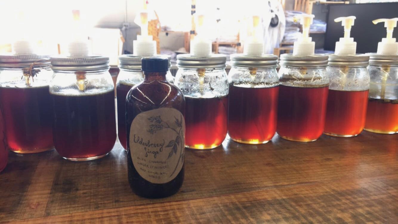 Kathleen's homemade elderberry syrup among the Wild Mountain Bees honeys.