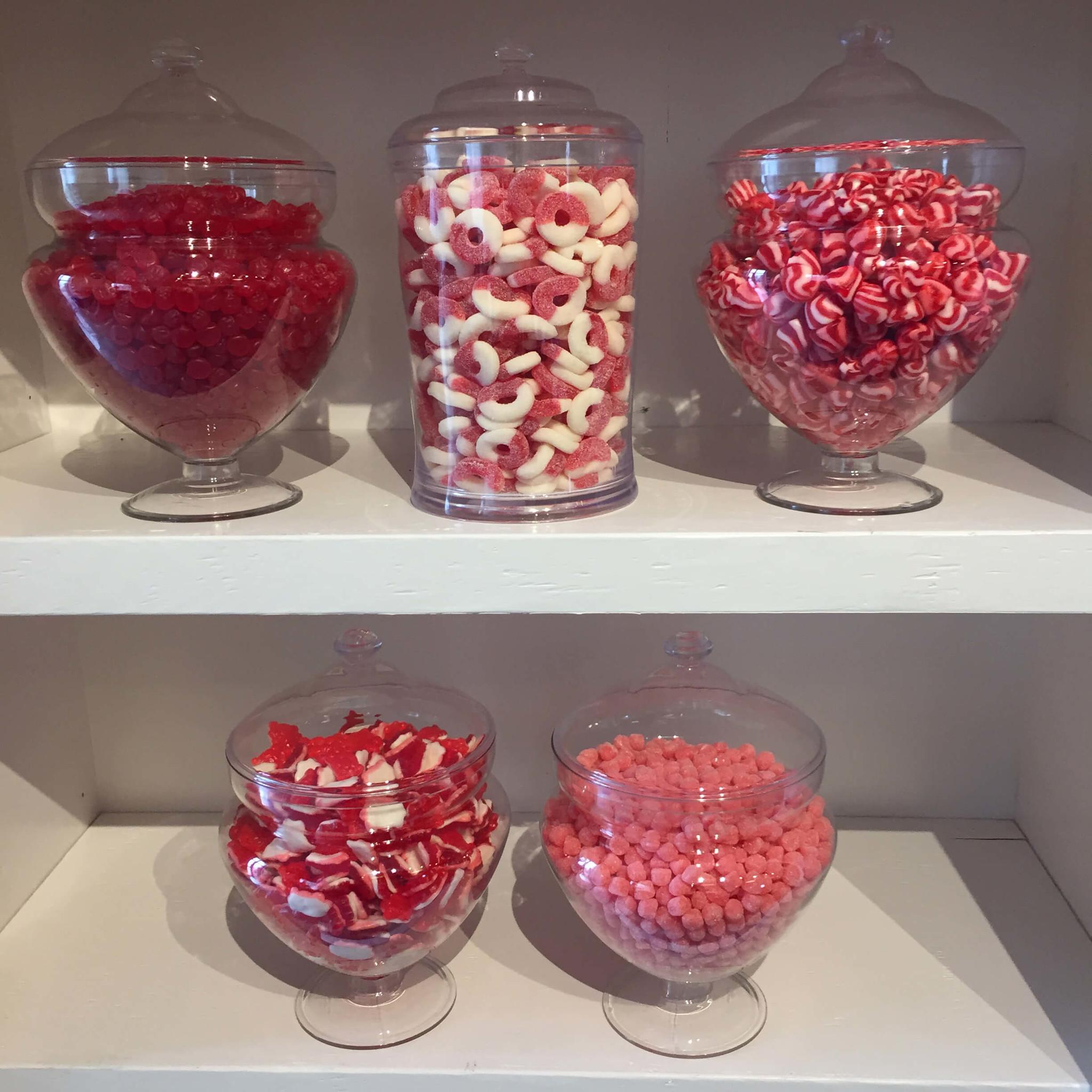 Bonbons rouges dans des pots sur des étagères