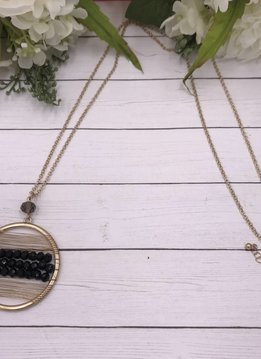 Gold Long Necklace with a Circle Pendant That Has Black Beads