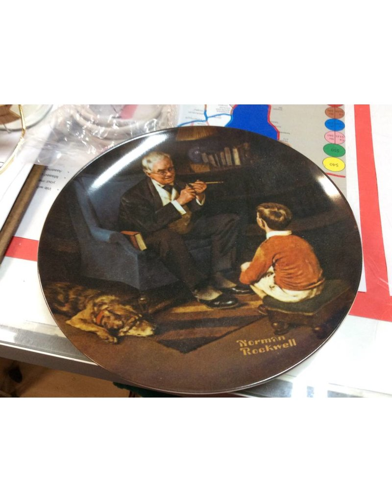 Decor plate man sitting in chair taking to boy