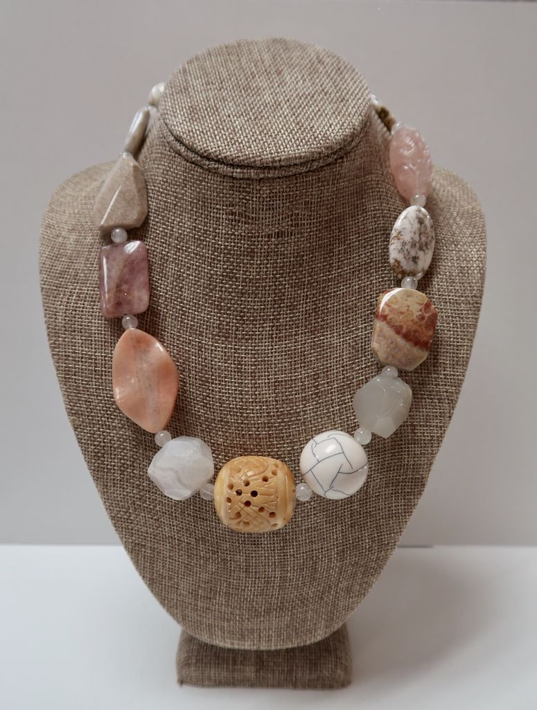 Beverly Creamer AABC5 – Polished stones and carved bone and carved pink jade in a cream and pink-toned necklace with white jade spacers