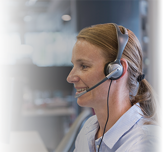 Female customer support specialist with headset sitting at desk